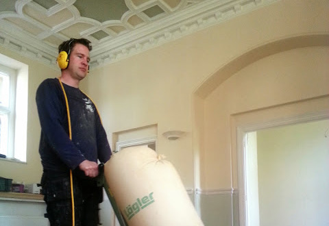 Tom using sanding machine in a house in gloucestershire